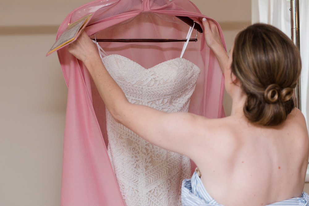 A bride getting ready and admiring her romantic lace wedding dress before her wedding at Oatlands Historic House and Gardens in Leesburg, Virginia