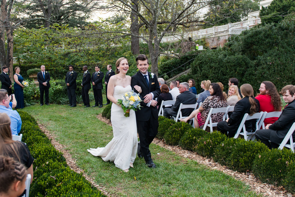 The bride and groom smile as their process out of their garden wedding ceremony at Oatlands Historic House and Gardens in Leesburg, Virginia