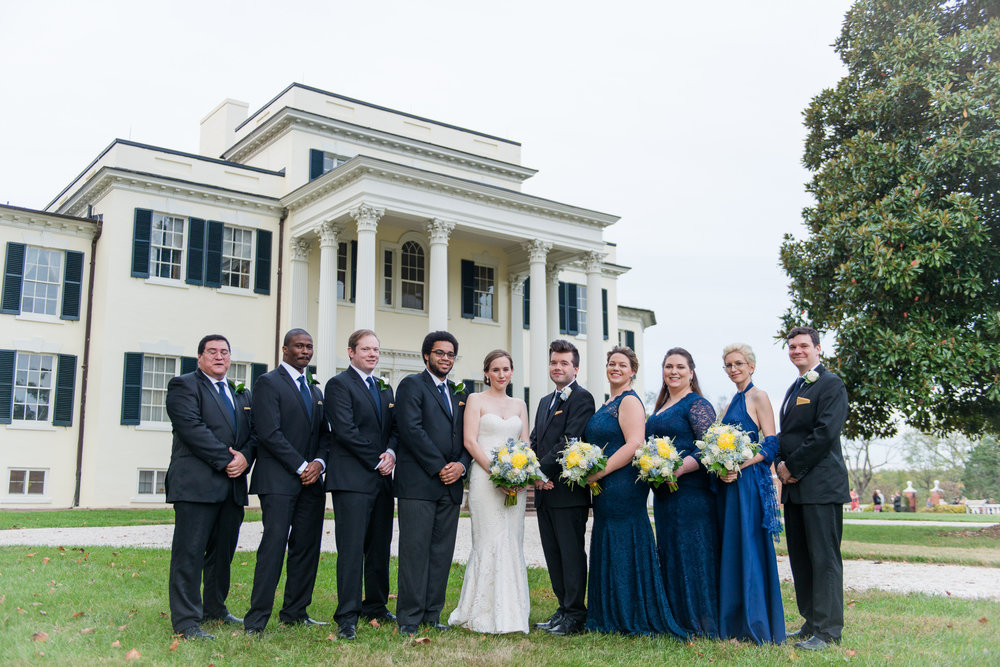 The bridal party pose in front of the historic house at Oatlands Historic House and Gardens in Leesburg, Virginia