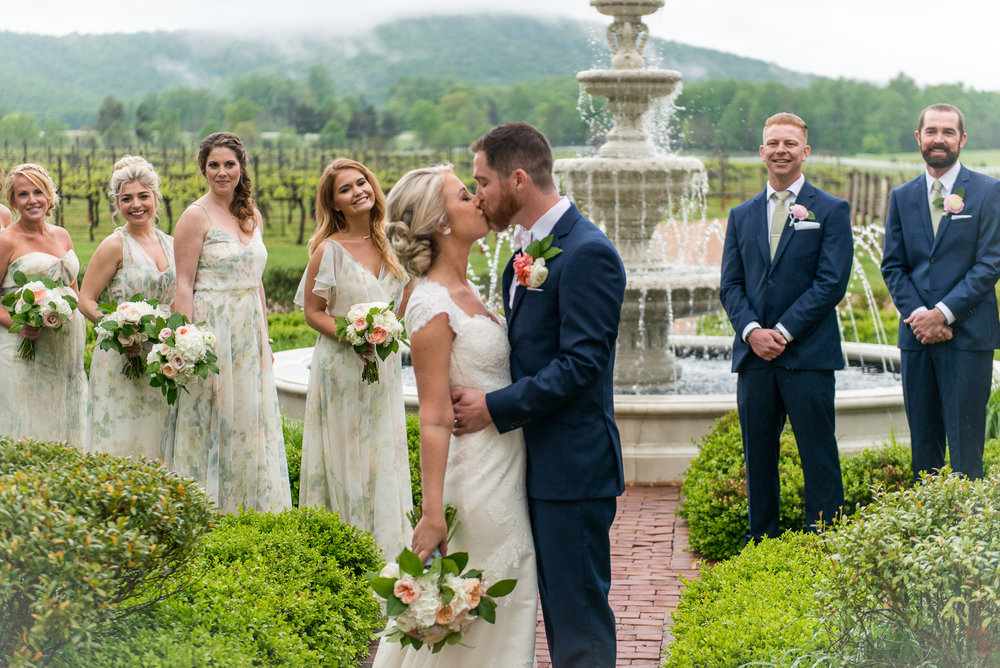 The wedding party surrounds the bride and groom as they kiss next to a fountain outside Keswick Vineyards in Charlottesville, Virginia