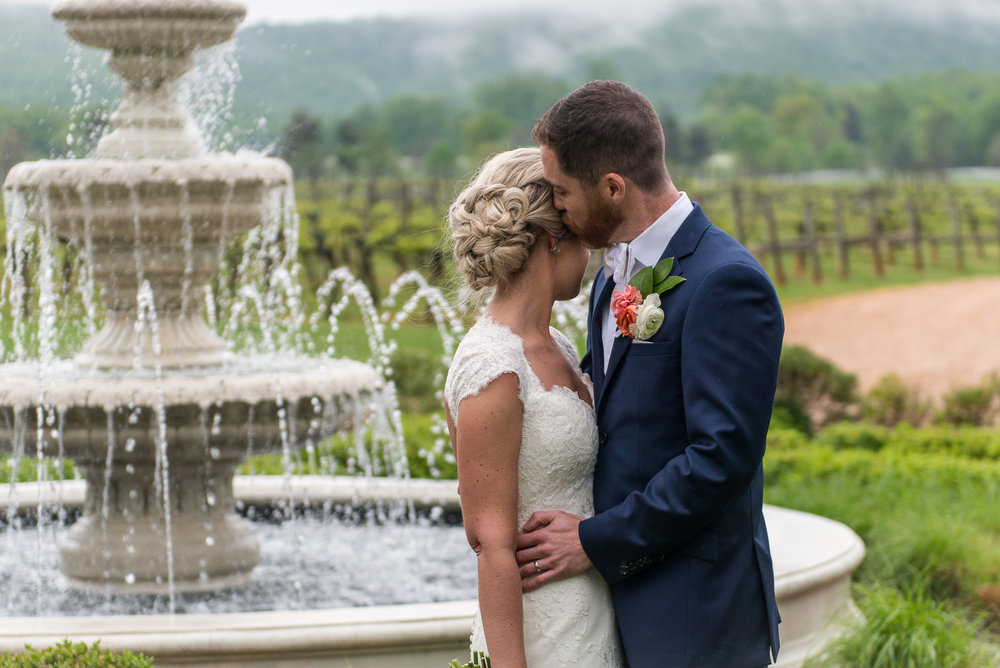 The bride and groom embrace as he kisses her temple next to a water fountain outside Keswick Vineyards in Charlottesville, Virginia