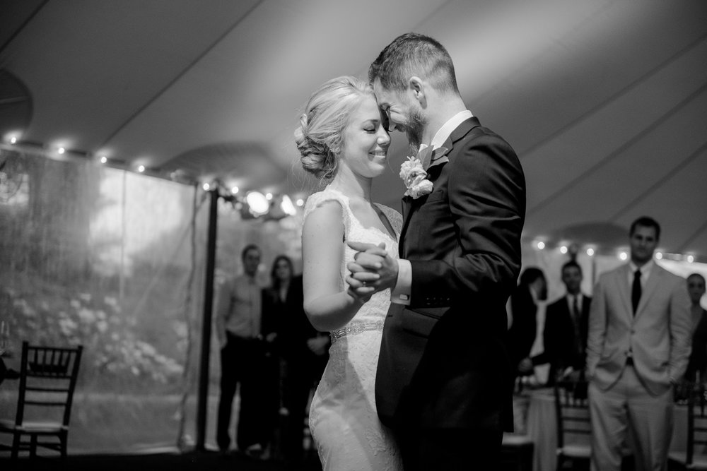The bride and groom share their first dance with smiles and touching foreheads during their wedding reception at Keswick Vineyards in Charlottesville, Virginia