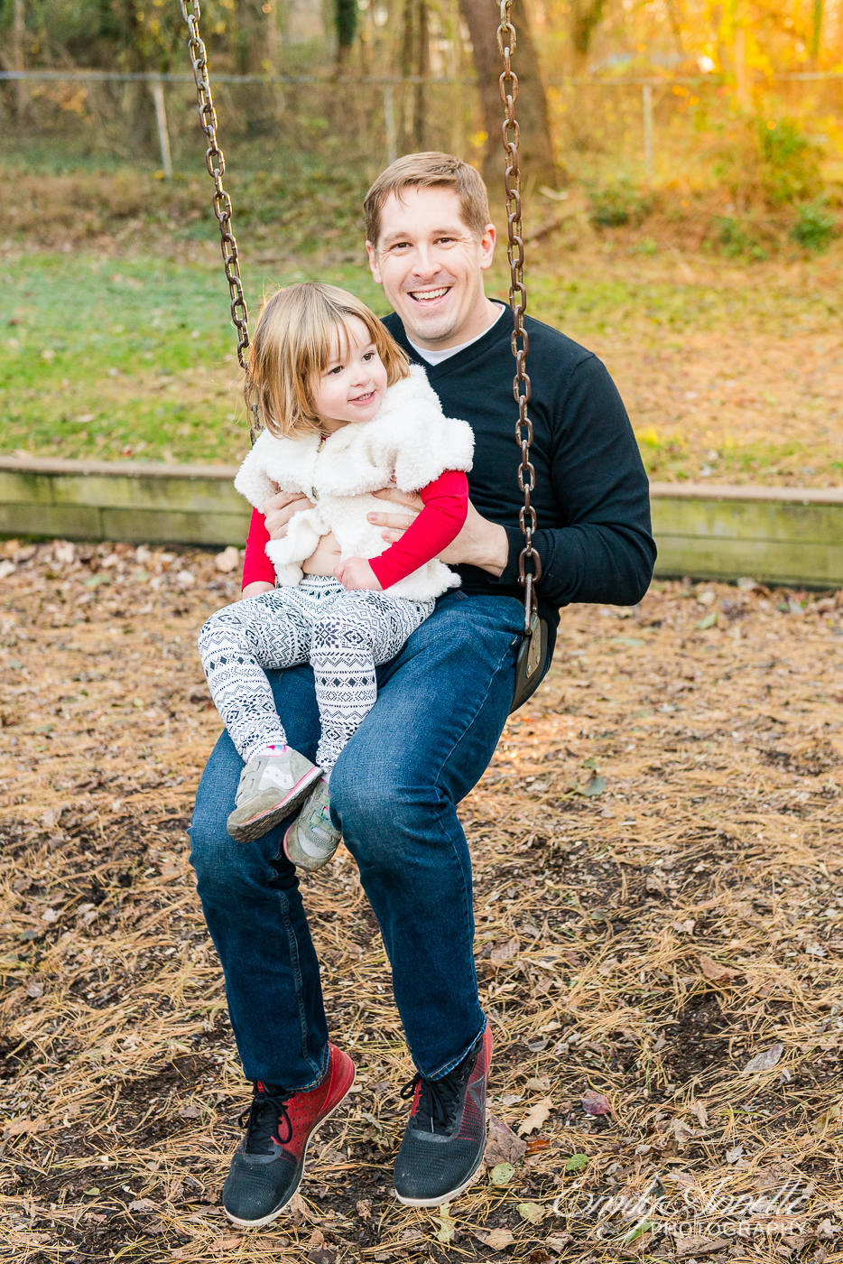 A young girl playing on the swings with her dad at Clifton Town Park in Fairfax County, Virginia