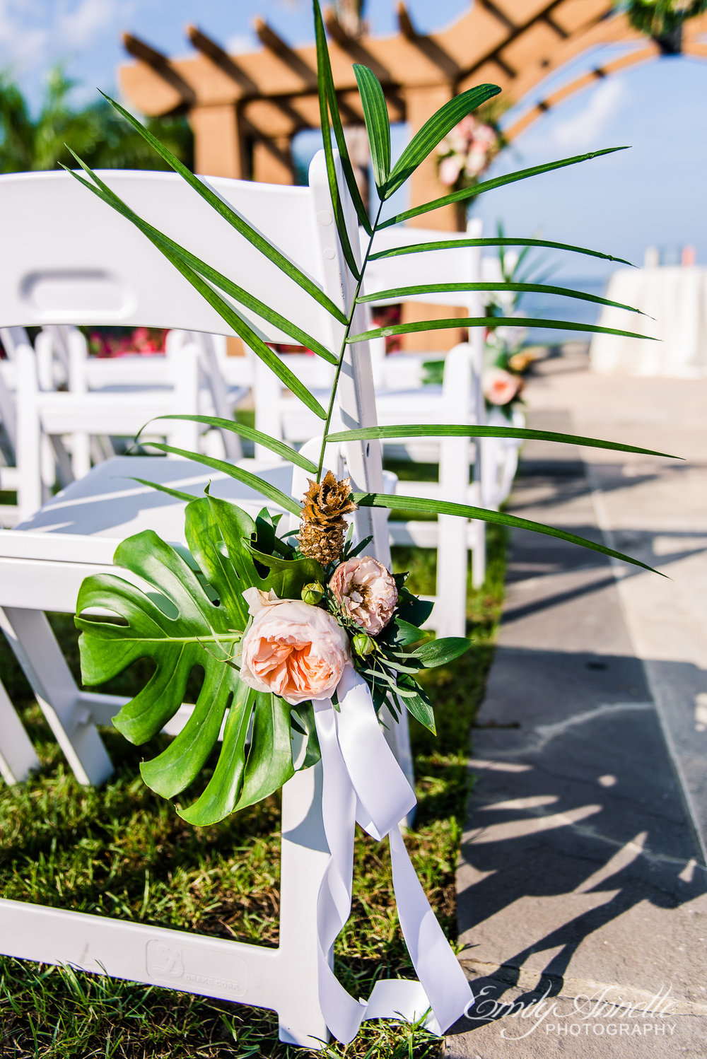 A tropical flower aisle decoration at the ceremony site before a wedding at Herrington on the Bay in North Beach, Maryland