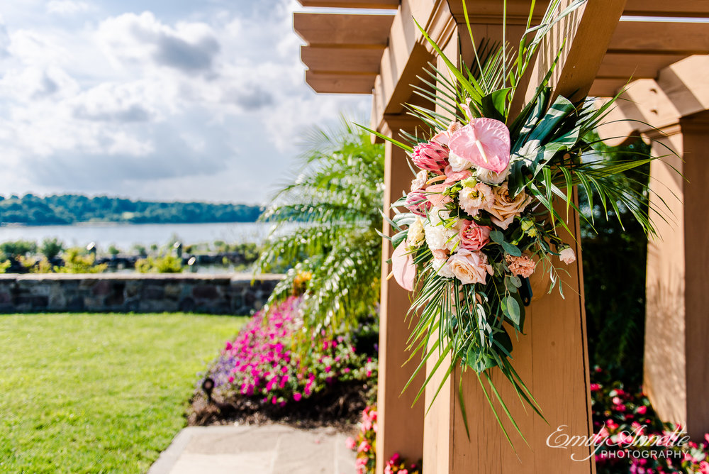 Tropical flowers decorating the ceremony site overlooking the Chesapeake Bay before a wedding at Herrington on the Bay in North Beach, Maryland