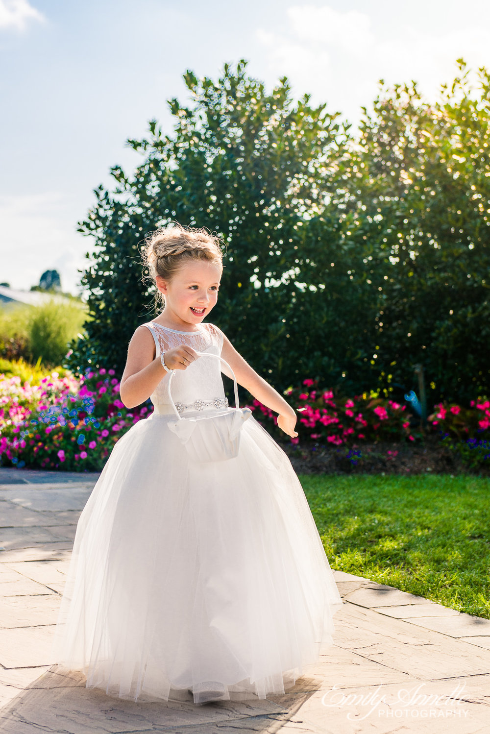 A flower girl in a big white dress drops petals during a wedding at Herrington on the Bay in North Beach, Maryland