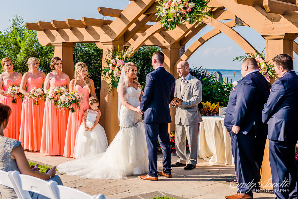 The wedding party stands at the front of the ceremony site as the bride and groom hold hands and say their vows during a wedding at Herrington on the Bay in North Beach, Maryland
