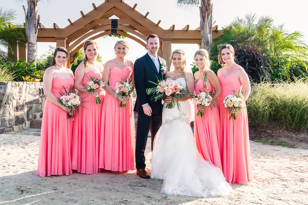 The bride and groom pose with their bridesmaids on the beach behind their ceremony site at Herrington on the Bay in North Beach, Maryland