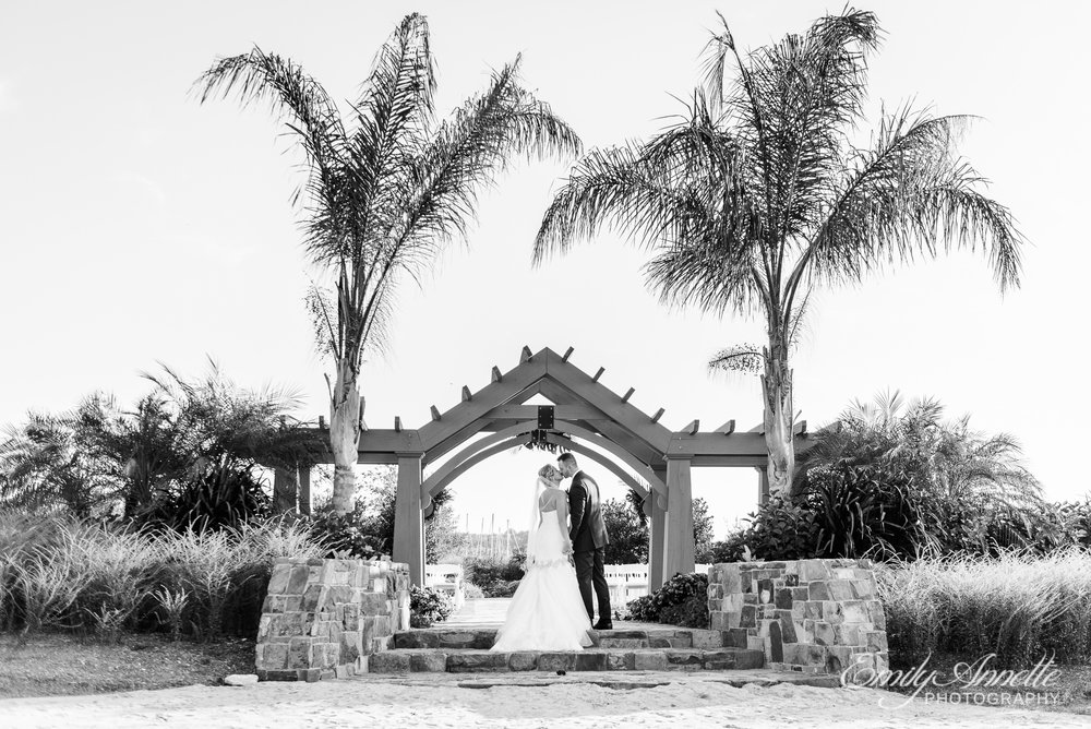 The bride and groom pose for a kiss on the beach in front of their wedding ceremony site at Herrington on the Bay in North Beach, Maryland