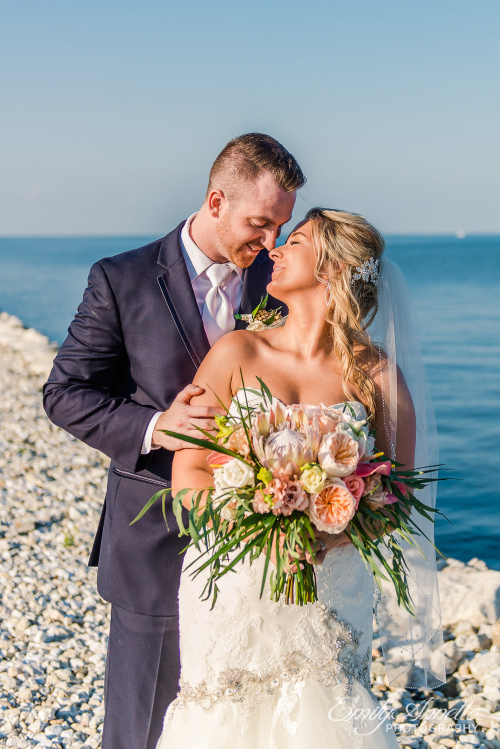A bride and groom embrace while surrounded by water on their wedding day at Herrington on the Bay in North Beach, Maryland