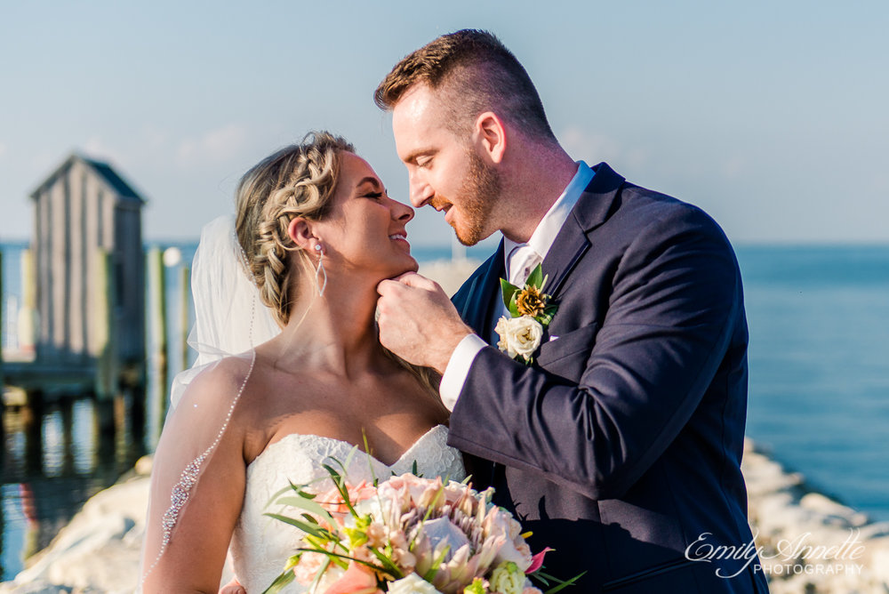 A bride and groom share a kiss while surrounded by water on their wedding day at Herrington on the Bay in North Beach, Maryland