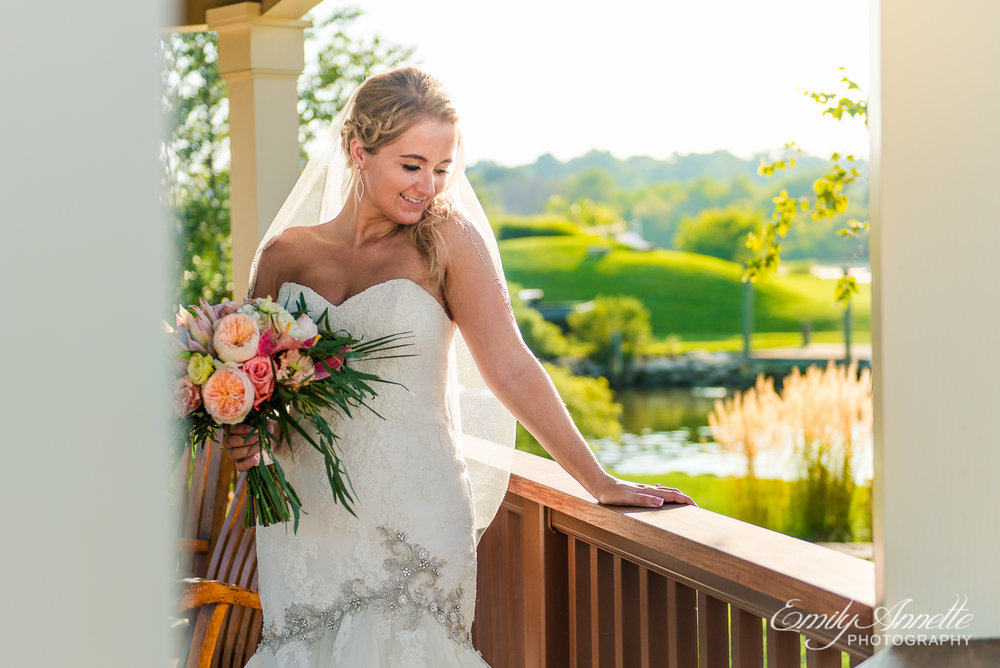 A bride poses while holding her tropical flower bouquet in a gazebo at Herrington on the Bay in North Beach, Maryland