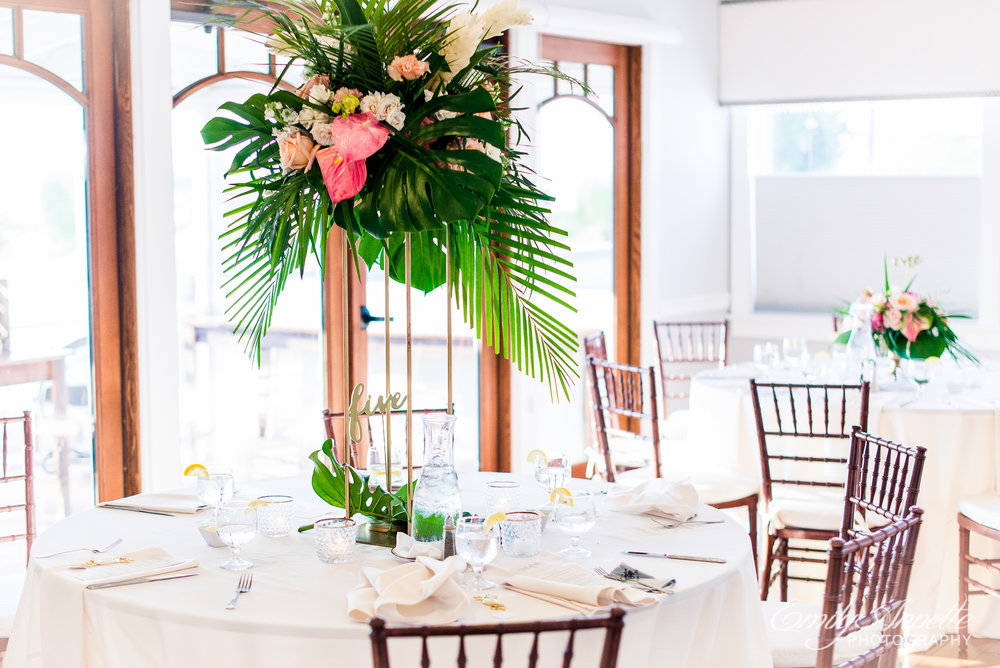 A reception ceremony decorated with big tropical flower arrangements at Herrington on the Bay in North Beach, Maryland