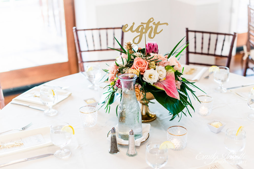 The tablescape for a wedding reception with tropical flower arrangements at Herrington on the Bay in North Beach, Maryland