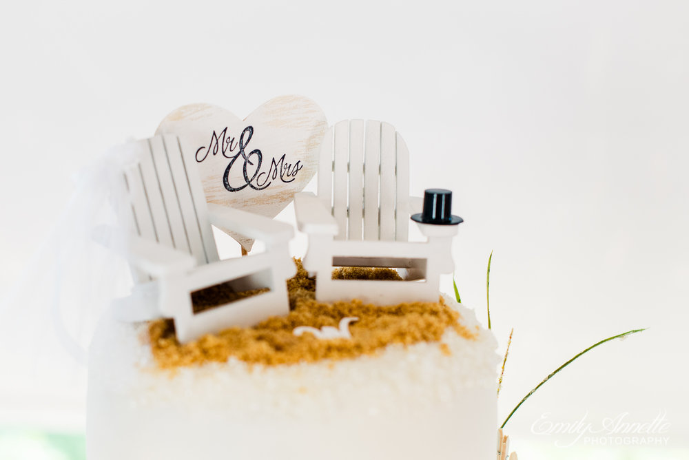 A beachy cake topper with two chairs and a monogram sitting on fake sand at the top of the wedding cake at Herrington on the Bay in North Beach, Maryland