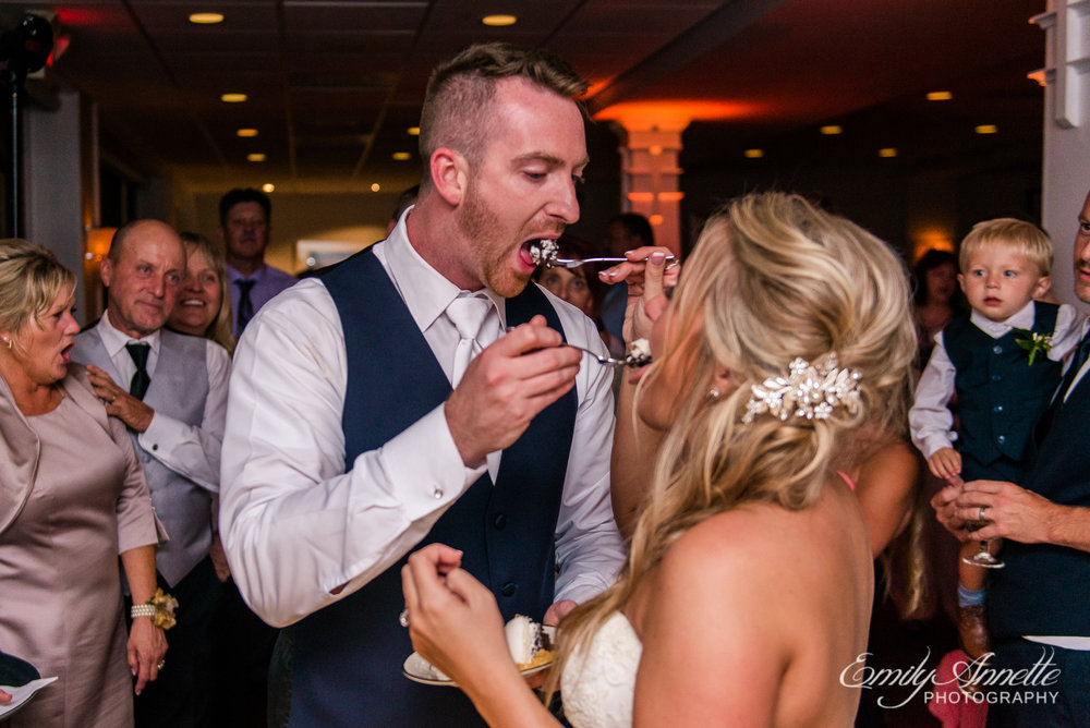 The bride and groom feed each other cake during their wedding reception at Herrington on the Bay in North Beach, Maryland