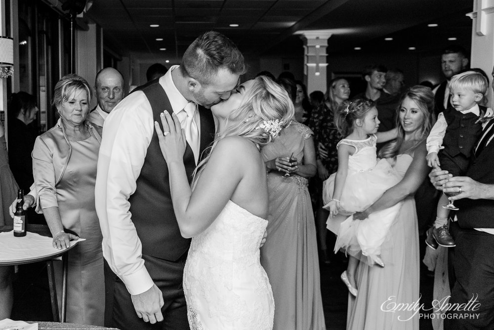 A bride and groom share a kiss during their wedding reception at Herrington on the Bay in North Beach, Maryland
