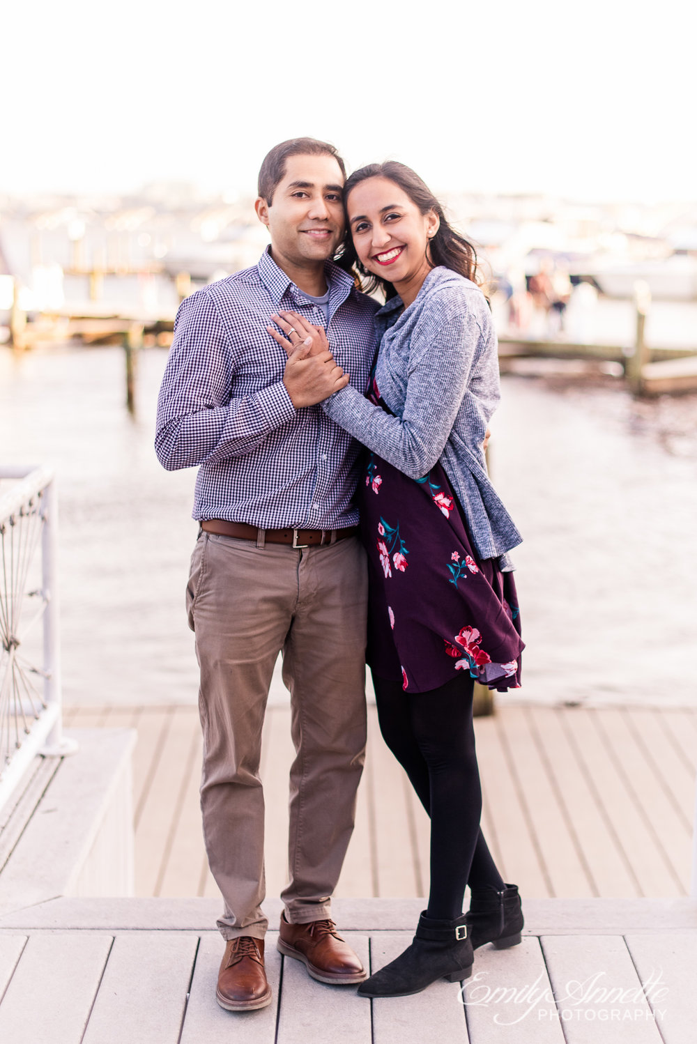An engaged couple poses by the Potomac River docks in Old Town Alexandria Virginia for an engagement session