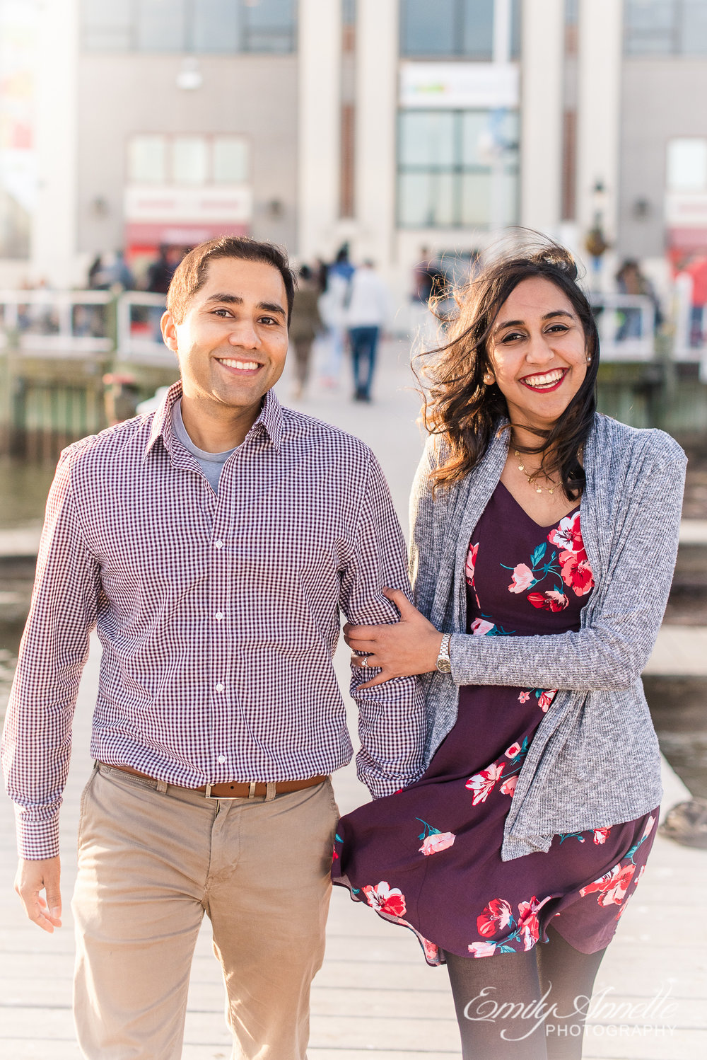 An engaged couple walks along the Potomac River docks in Old Town Alexandria Virginia for an engagement session