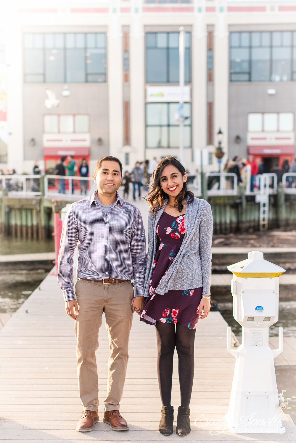 An engaged couple poses along the Potomac River docks in Old Town Alexandria Virginia for an engagement session