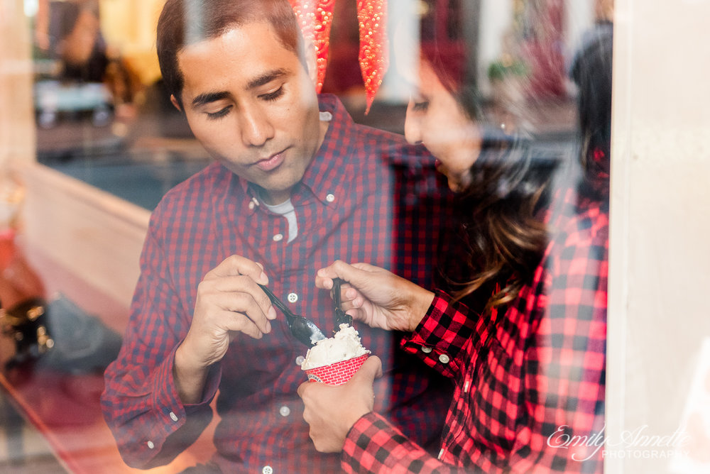 An engaged couple shares ice cream from Pops Old Fashioned Ice Cream during an engagement session in Old Town Alexandria Virginia