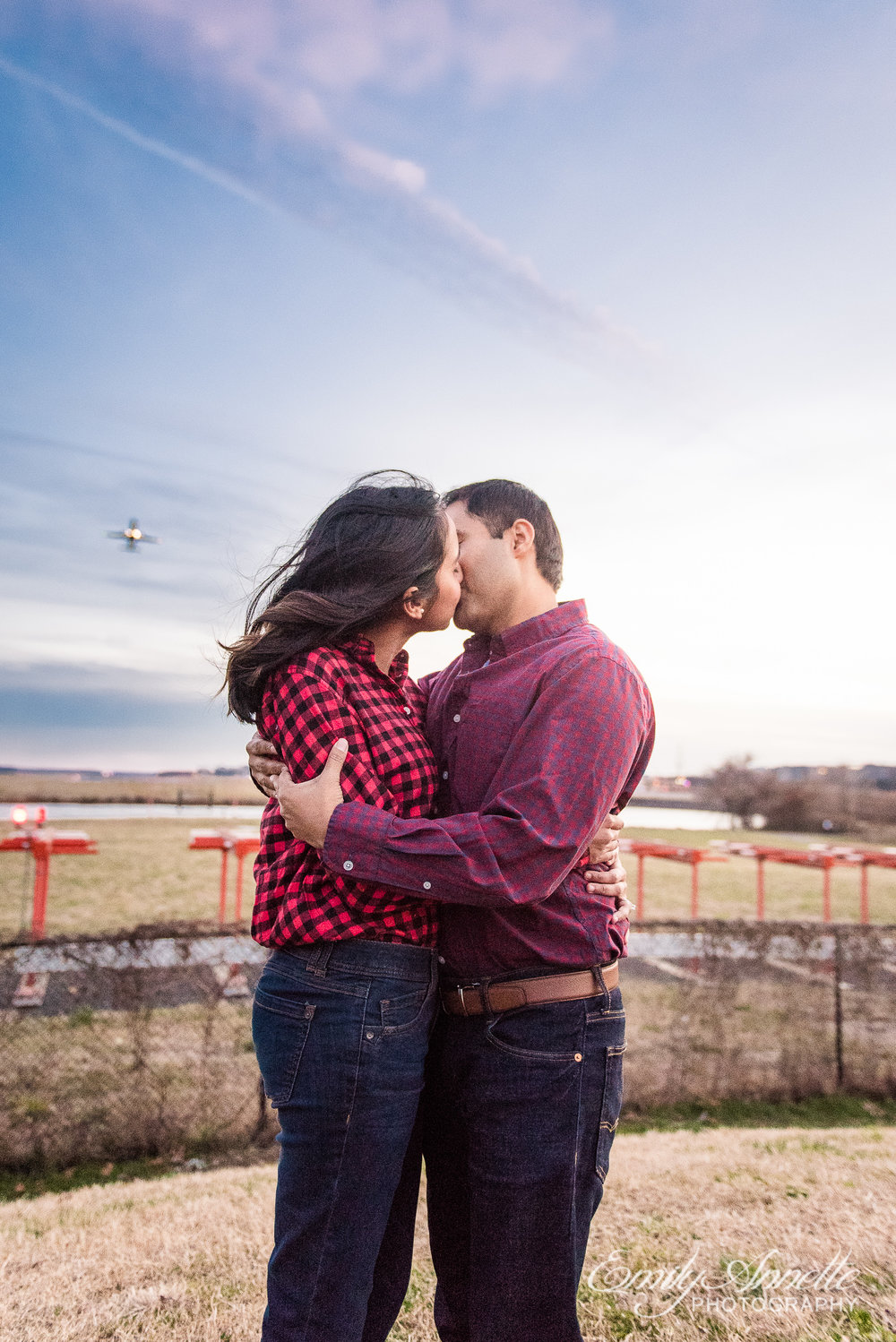 An engaged couple shares a kiss as planes take off from Reagan International Airport in the background while at Gravelly Point Park in Arlington Virginia for an engagement session