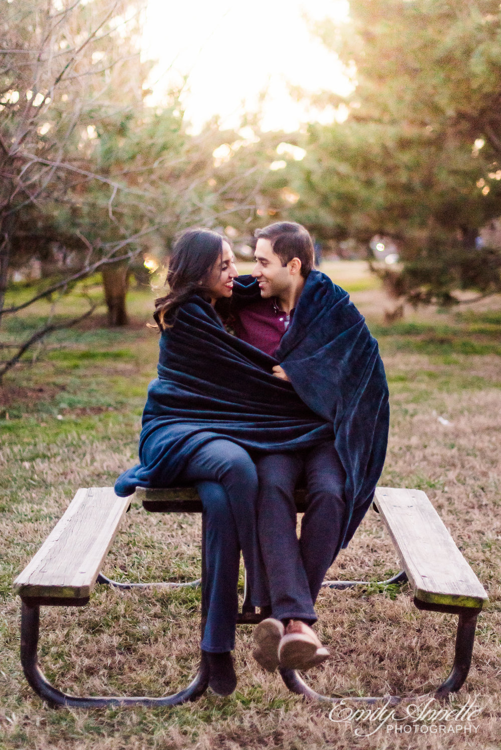 An engaged couple smiles at each other while wrapped in a blanket sitting on a picnic table at Gravelly Point Park in Arlington Virginia for an engagement session