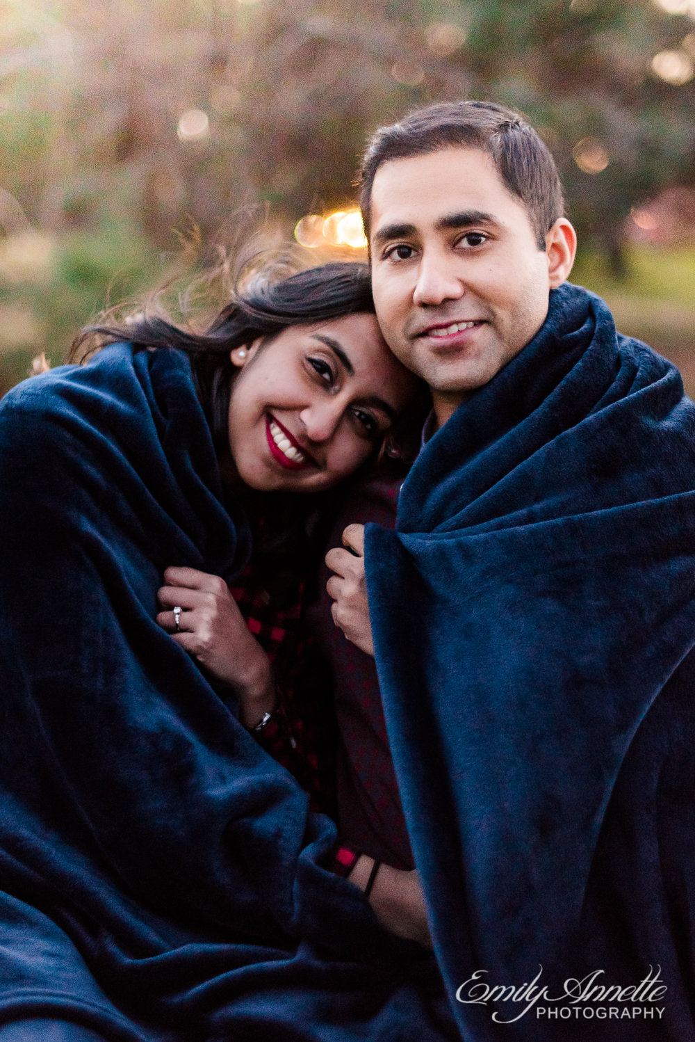 An engaged couple snuggles while wrapped in a blanket sitting on a picnic table at Gravelly Point Park in Arlington Virginia for an engagement session