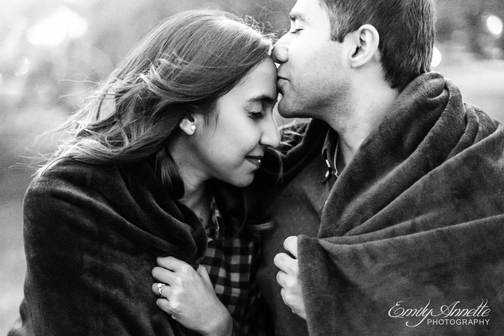 A man kisses the forehead of his fiancee while wrapped in a blanket sitting on a picnic table at Gravelly Point Park in Arlington Virginia for an engagement session