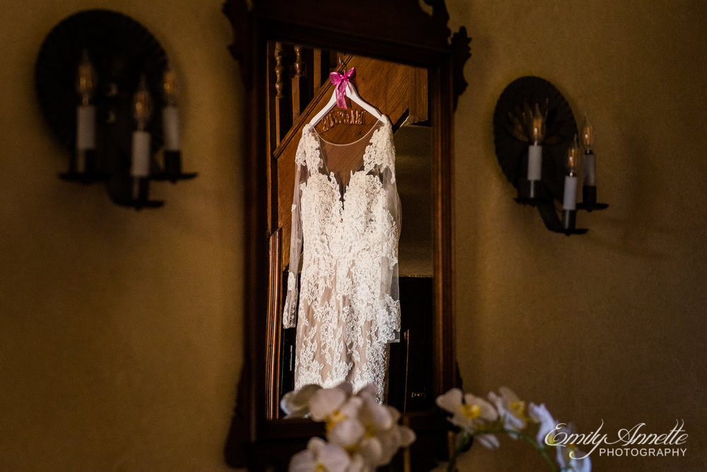 View through a mirror of bridal details of a lace wedding dress with sleeves hanging from the stairs while the bride is getting ready at Willow Oaks Country Club in Richmond, Virginia