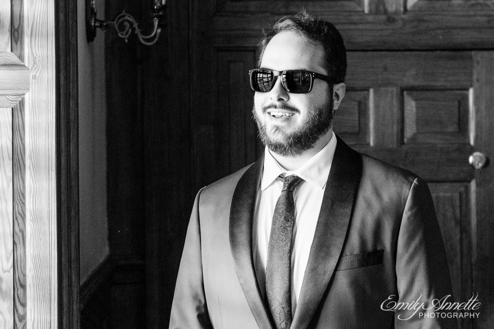 A groom wearing sunglasses while getting ready before his wedding at Willow Oaks Country Club in Richmond, Virginia