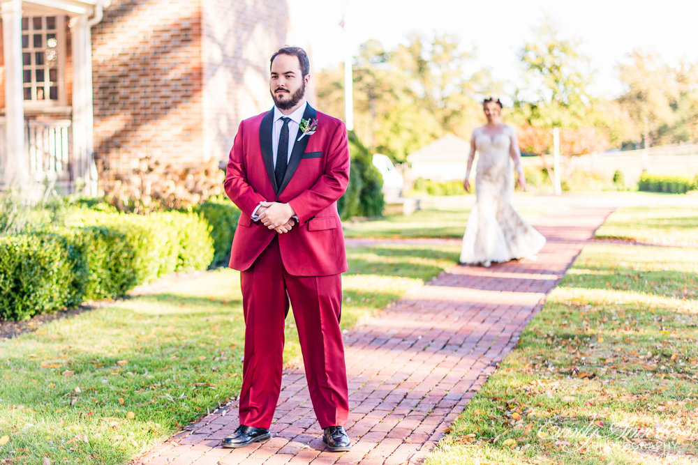 A groom in a red suit waiting for his bride as she approaches for their first look before their wedding ceremony at Willow Oaks Country Club in Richmond, Virginia