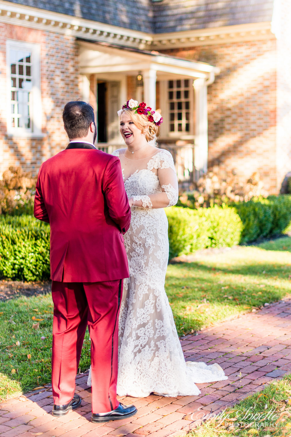 A bride in a lace wedding dress with sleeves laughing as she looks at her groom for the first time for their first look before their wedding ceremony at Willow Oaks Country Club in Richmond, Virginia