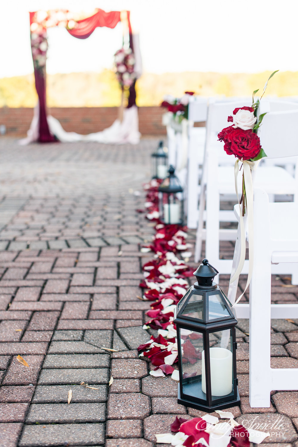 Ceremony site decorations including lanterns, rose petals, and flower bouquets on chairs at Willow Oaks Country Club in Richmond, Virginia