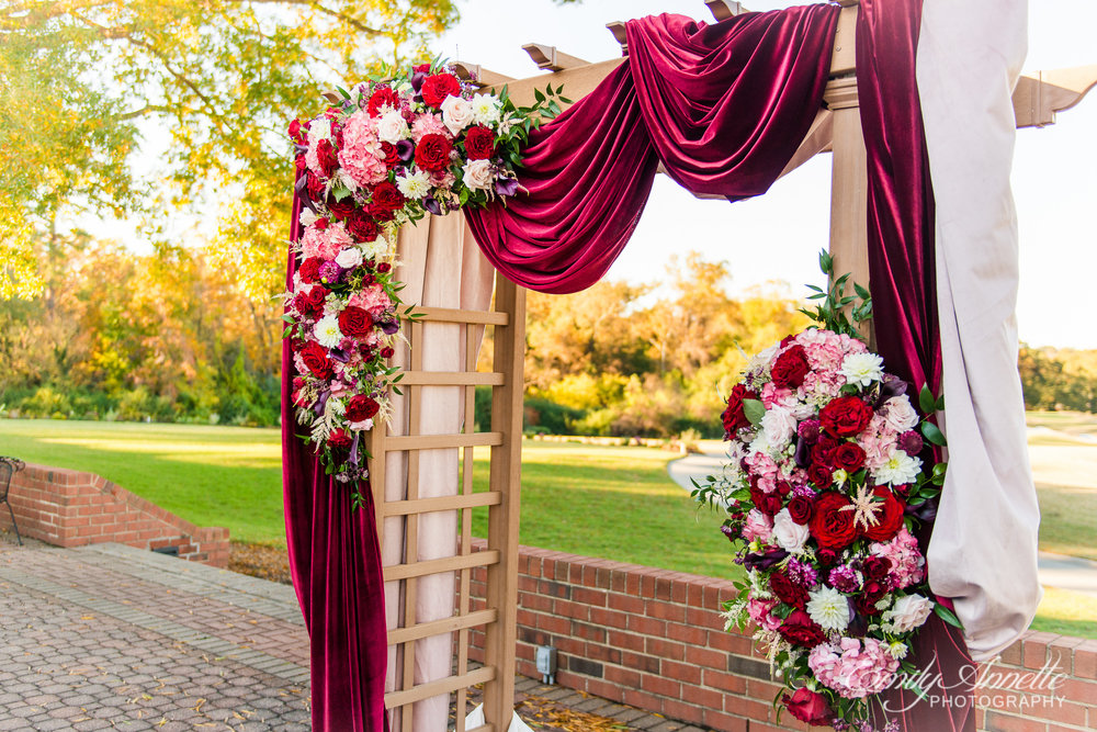 A red and pink decorated arch for a wedding ceremony at Willow Oaks Country Club in Richmond, Virginia