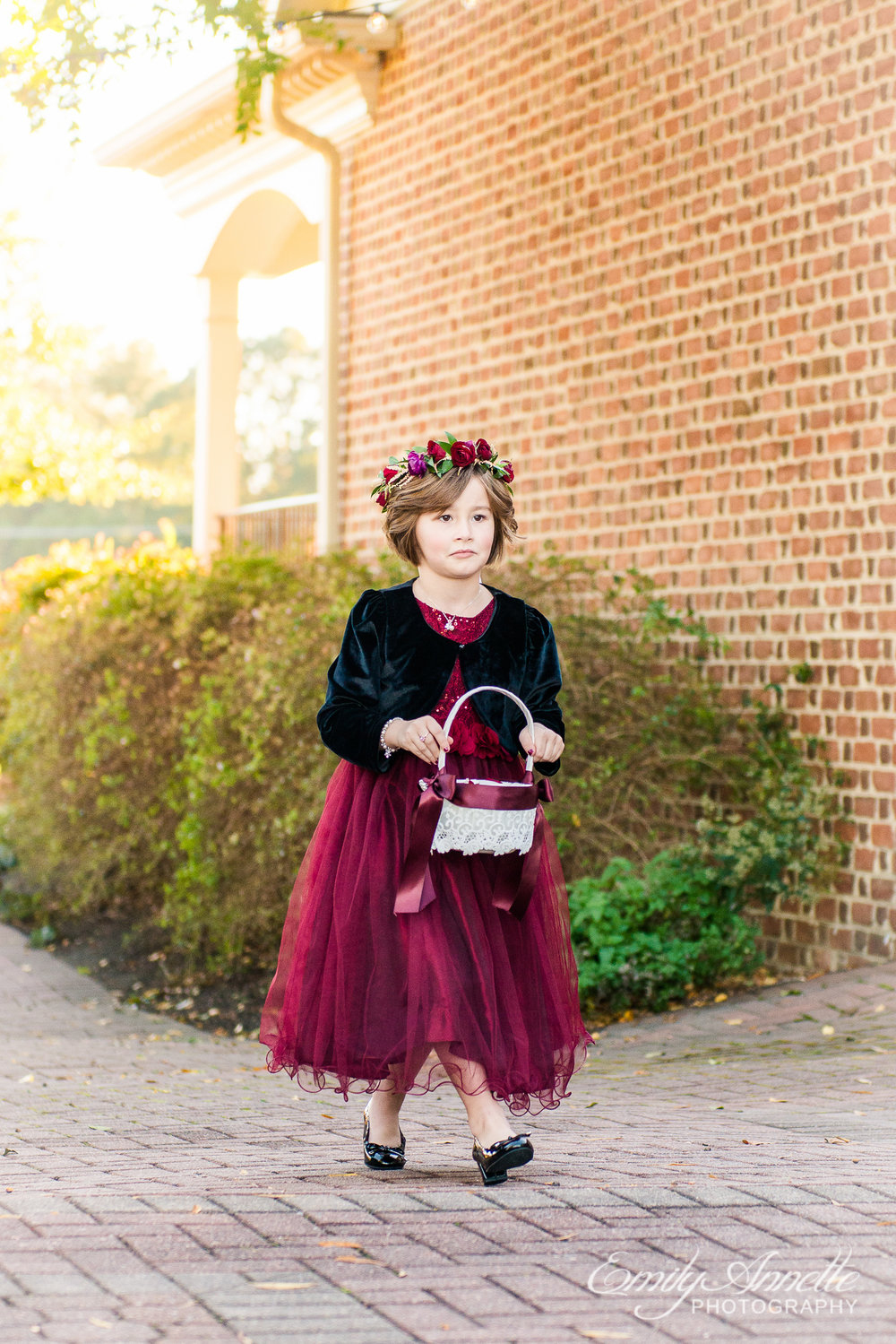 A flower girl in a red dress and flower crown walking into the wedding ceremony at Willow Oaks Country Club in Richmond, Virginia