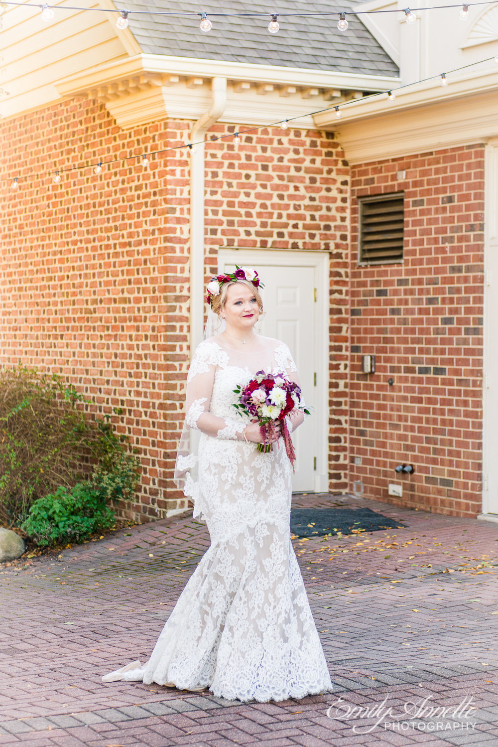 A bride in a lace wedding dress with sleeves walking into the wedding ceremony at Willow Oaks Country Club in Richmond, Virginia