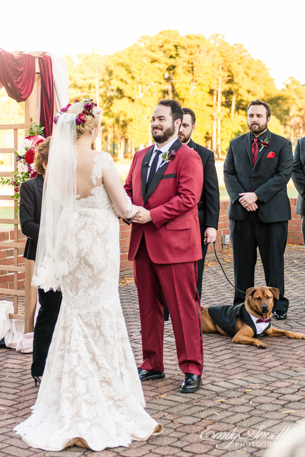 A groom in a red suit looking at his bride during an outdoor wedding ceremony at Willow Oaks Country Club in Richmond, Virginia
