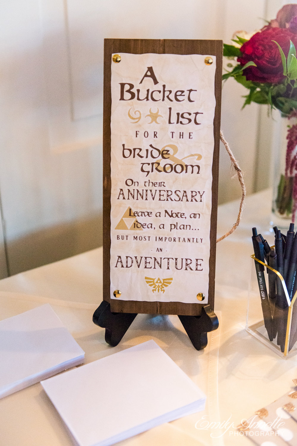 A sign asking guests to write down bucket list ideas for the bride and groom at a wedding reception at Willow Oaks Country Club in Richmond, Virginia