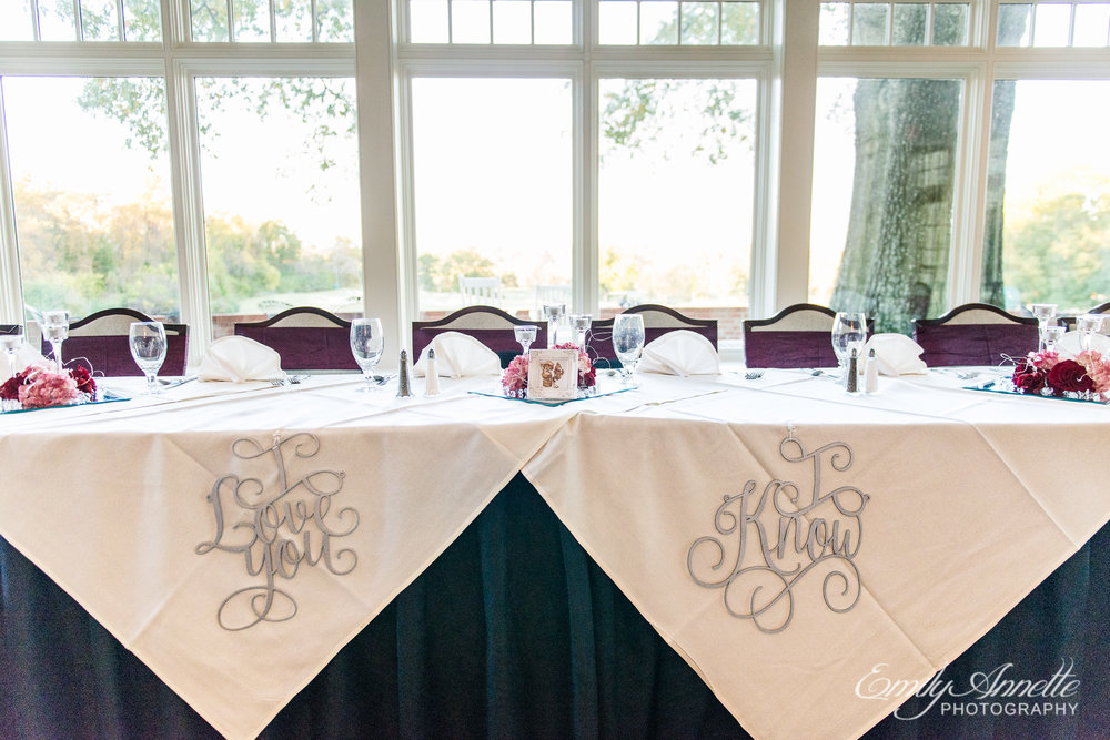 "A wedding party head table with signs that say ""I love you"" and ""I know"" referencing star wars at a wedding reception at Willow Oaks Country Club in Richmond, Virginia"