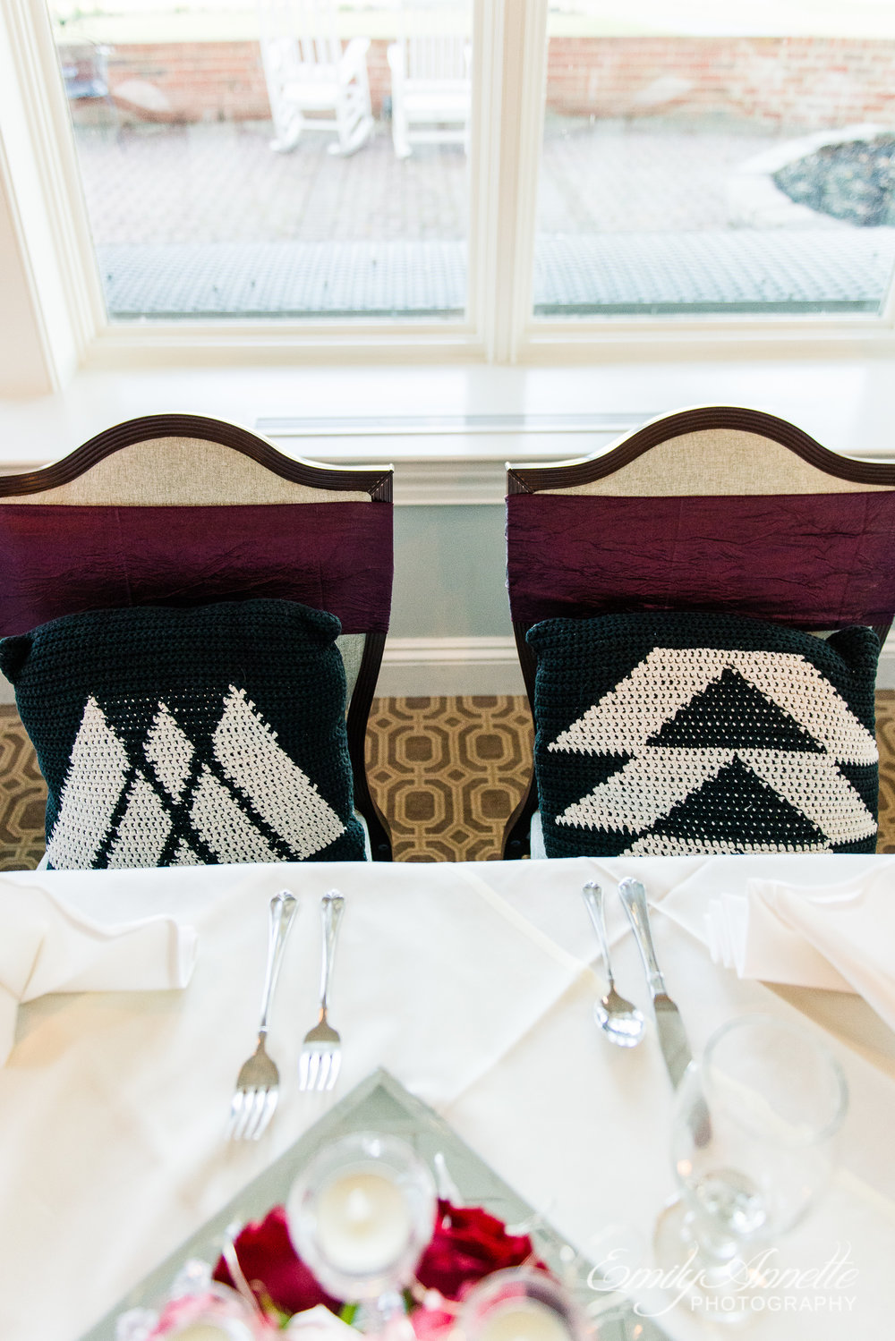 A sweetheart table with cushions that have video game references on them at a wedding reception at Willow Oaks Country Club in Richmond, Virginia