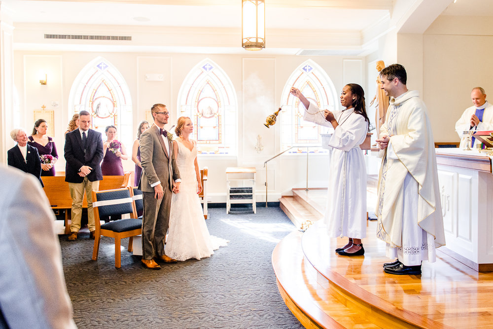A bride and groom stand together during a blessing with incense for a Catholic wedding ceremony at the Sacred Heart of Mary Chapel at Marymount University in Arlington, Virginia