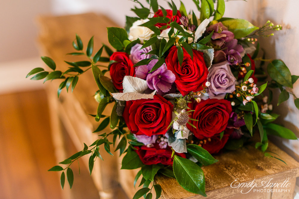 A bridal bouquet featuring red and purple flowers including red roses and greenery for a wedding at Fleetwood Farm Winery in Leesburg, Virginia