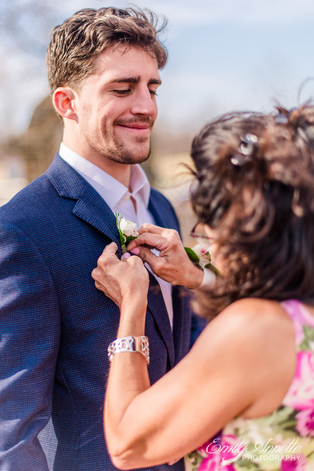 The mother of the groom pinning the boutonniere on her son the groom before his wedding at Fleetwood Farm Winery in Leesburg, Virginia