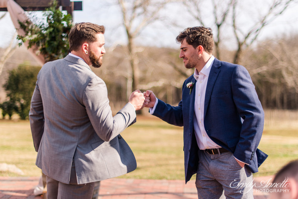 A groom giving a fist bump to a groomsman before his wedding at Fleetwood Farm Winery in Leesburg, Virginia