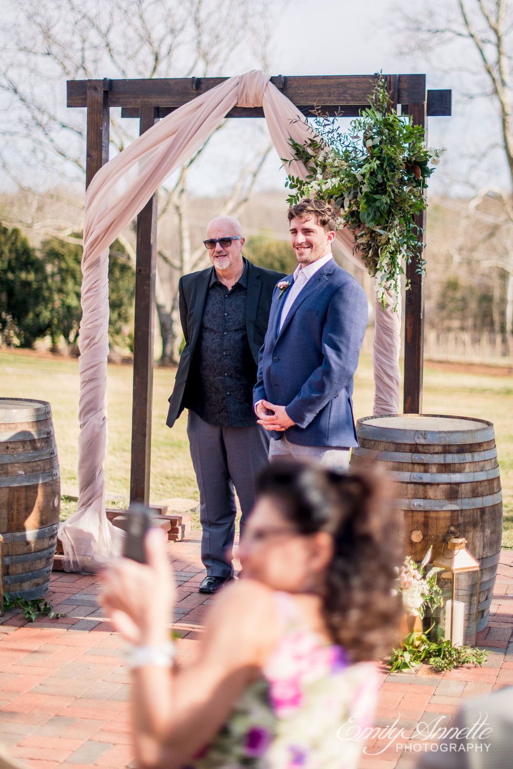 A groom seeing his bride walk down the aisle during their spring wedding at Fleetwood Farm Winery in Leesburg, Virginia