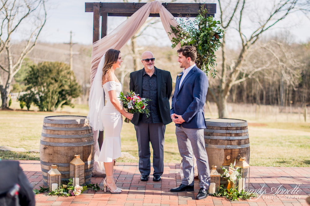 The bride and groom standing at the altar during their wedding ceremony at Fleetwood Farm Winery in Leesburg, Virginia