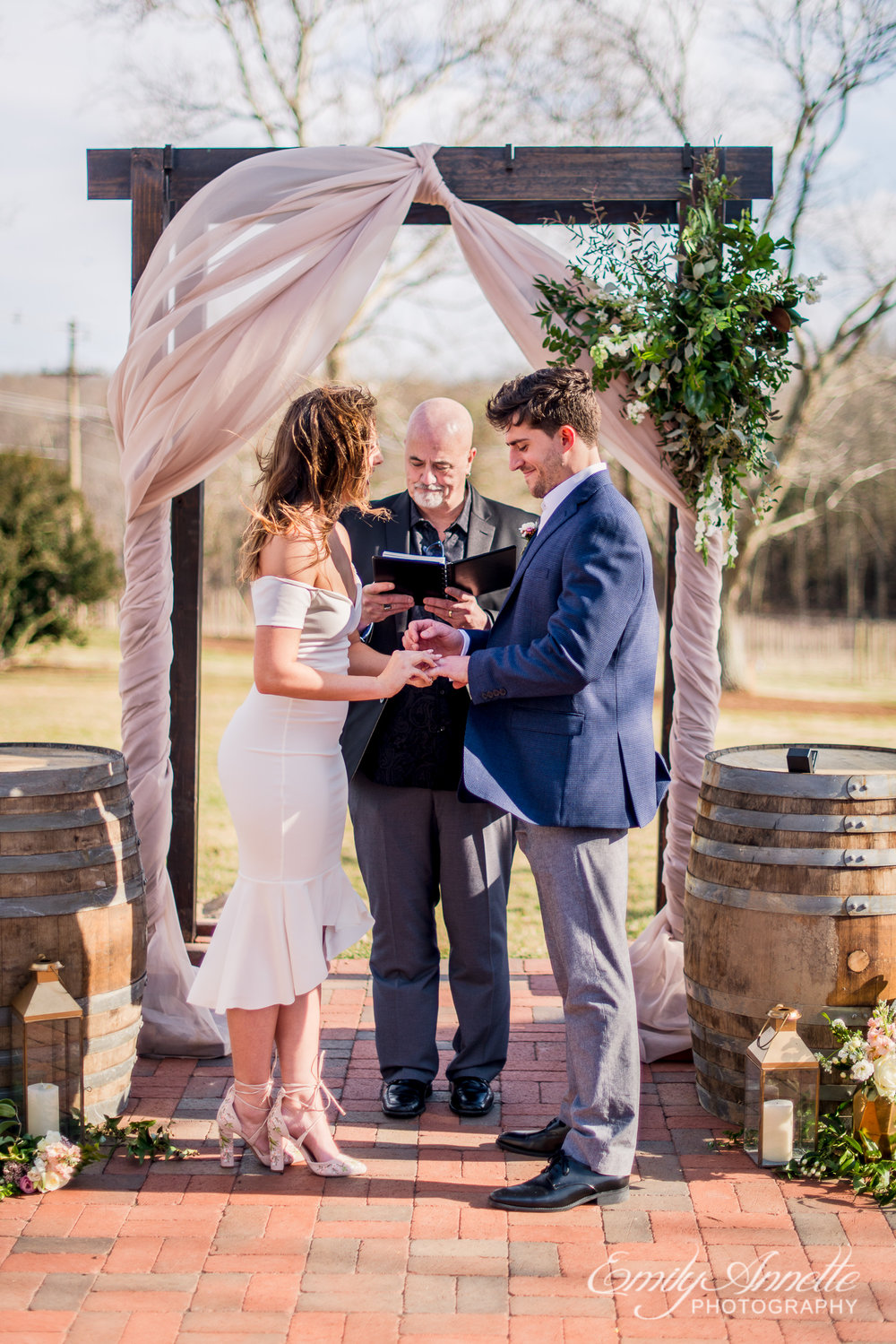 The bride and groom exchange rings during their wedding ceremony at Fleetwood Farm Winery in Leesburg, Virginia