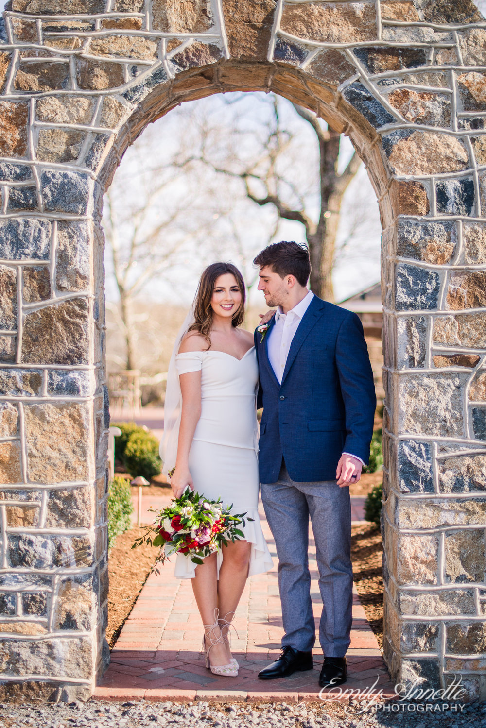 A bride and groom stand together under a stone arch on their wedding day at Fleetwood Farm Winery in Leesburg, Virginia