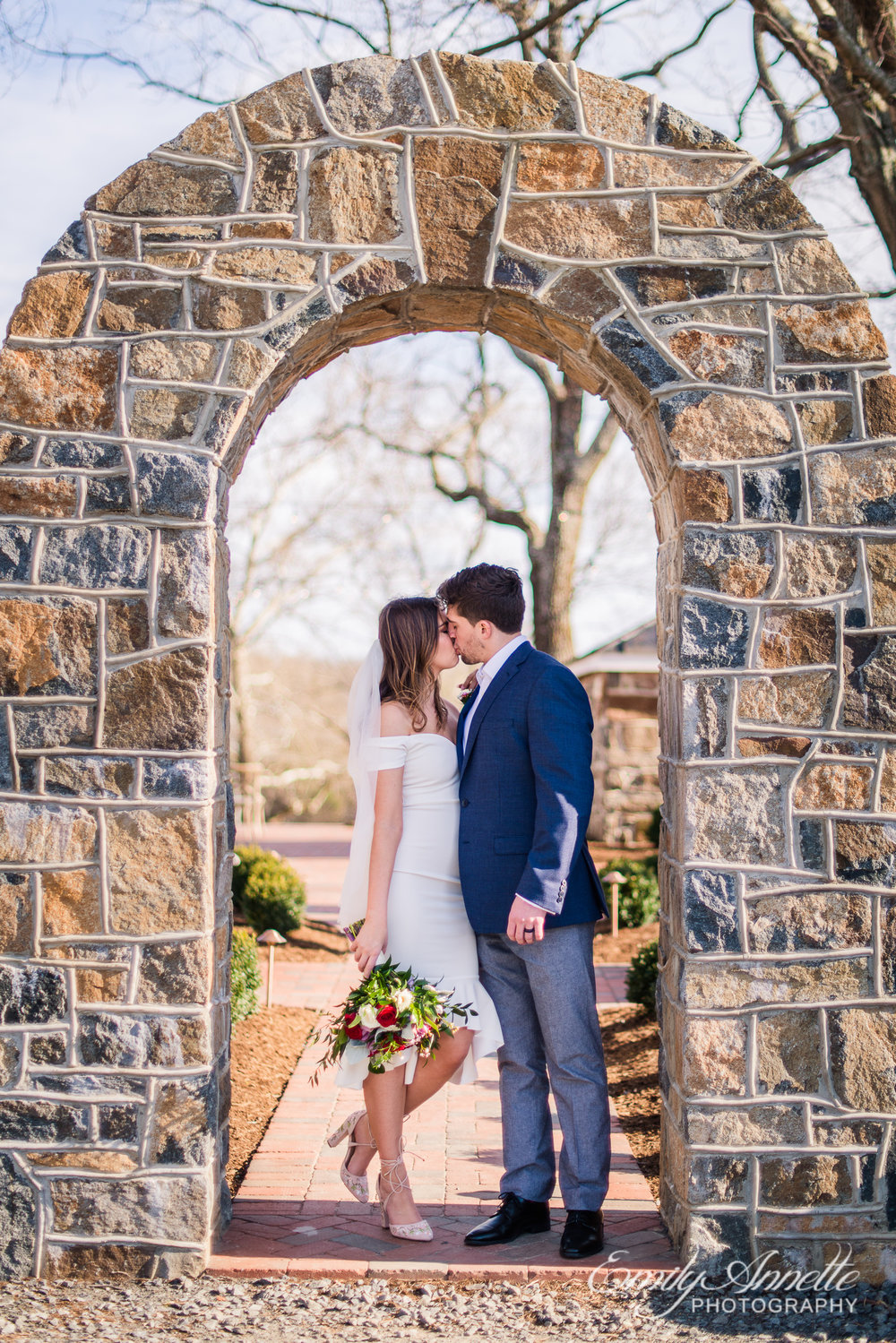 A bride and groom share a kiss while under a stone arch on their wedding day at Fleetwood Farm Winery in Leesburg, Virginia